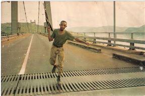 Junior on bridge with gun.
